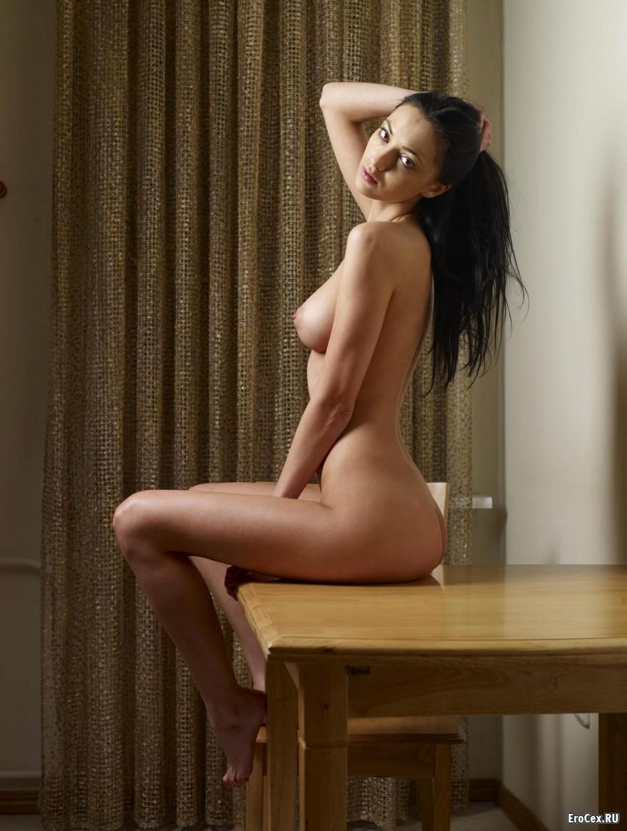 Голая девушка позирует на столе
