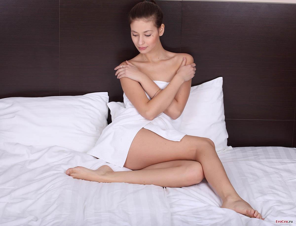 Голая девочка позирует на кровати